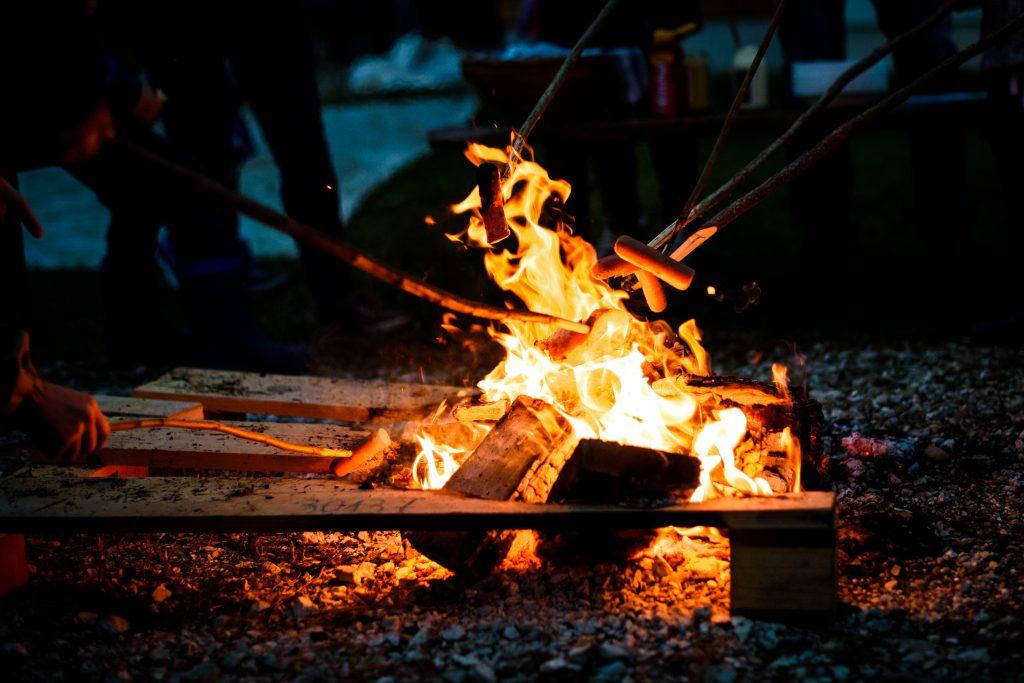 Bålsted der er tændt så det er muligt at lave mad henover ilden. Under over dækket bålhytte.