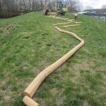 Lange træ stolper der ligger på græs
